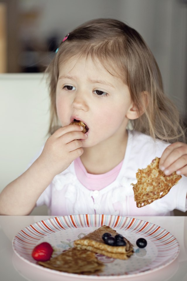 Little girl eating pancake.