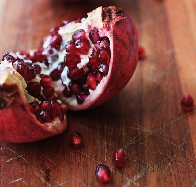 Freshly split pomegranate on a wooden chopping board