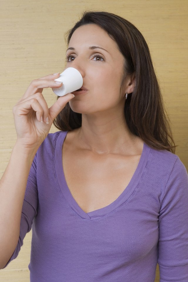 Close-up of a mid adult woman sipping from a mouthwash cup