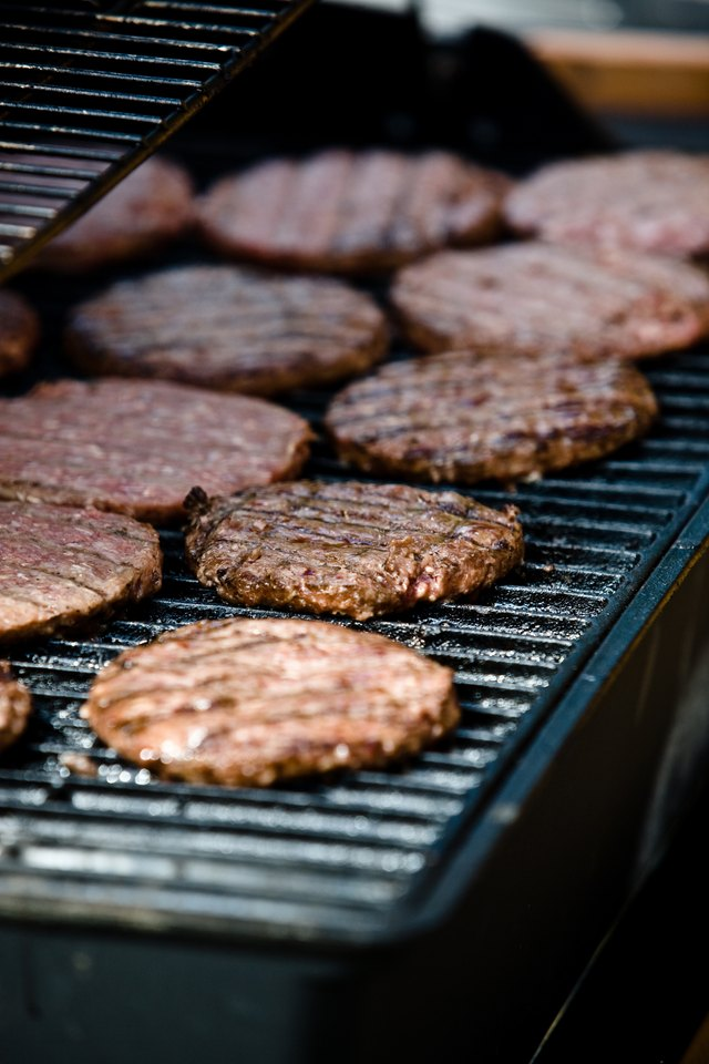 Hamburger patties cooking on outdoor grill