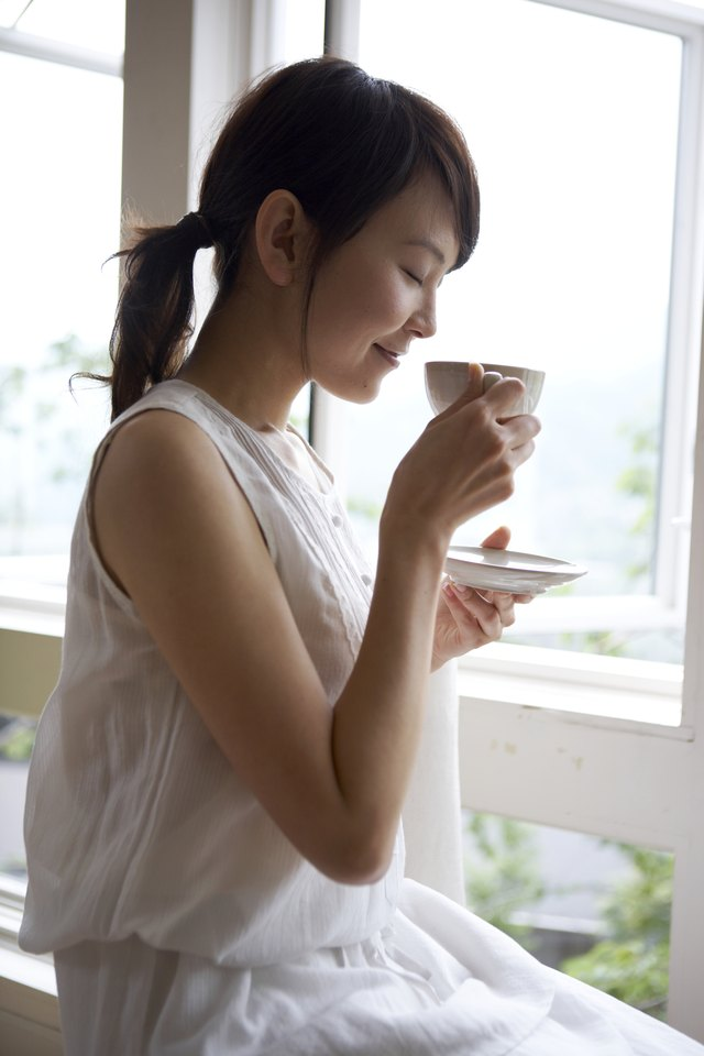 Woman drinking tea by window in home