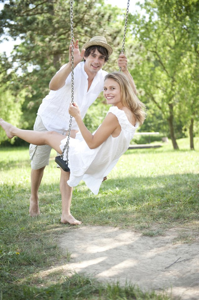 Portrait of young couple on swing in park