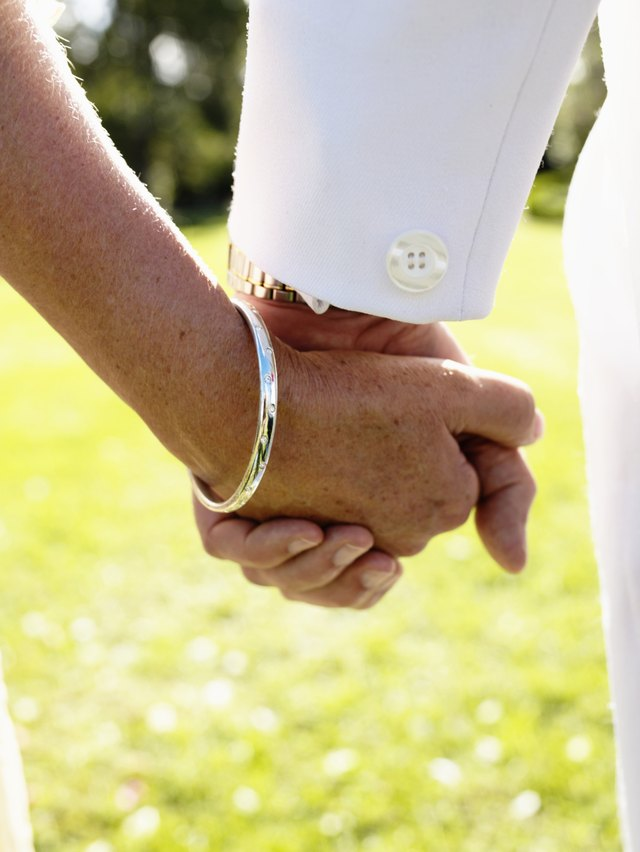 Bride and groom holding hands, close-up, rear view