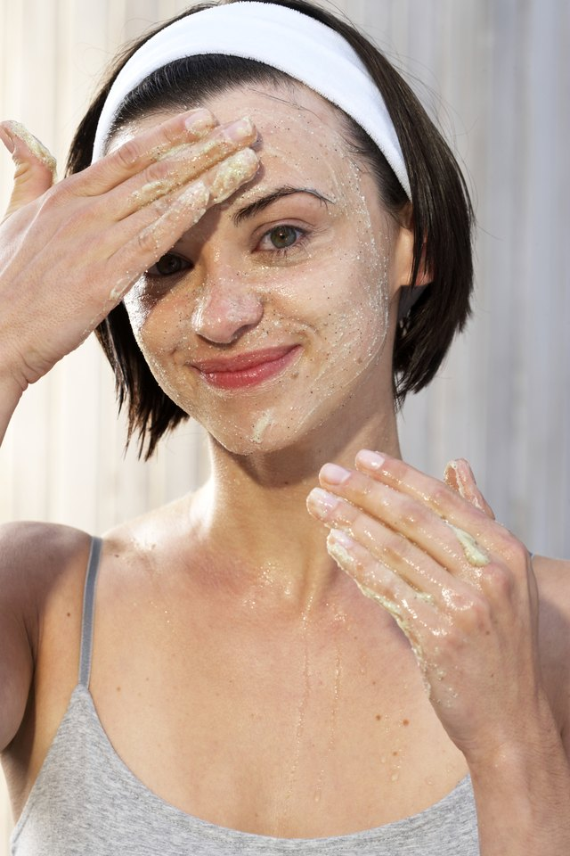 Young woman exfoliating face, smiling, portrait, close-up