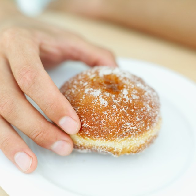 Close-up of a young man's hand holding a doughnut