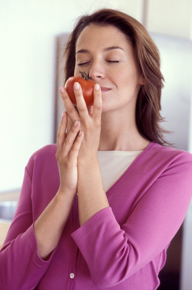 Woman inhaling scent of tomato