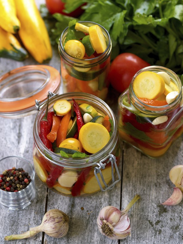 Preparing preserves of pickled zucchini in jars with spices, gar