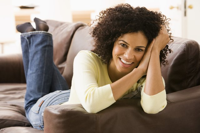 Smiling woman lying down on couch