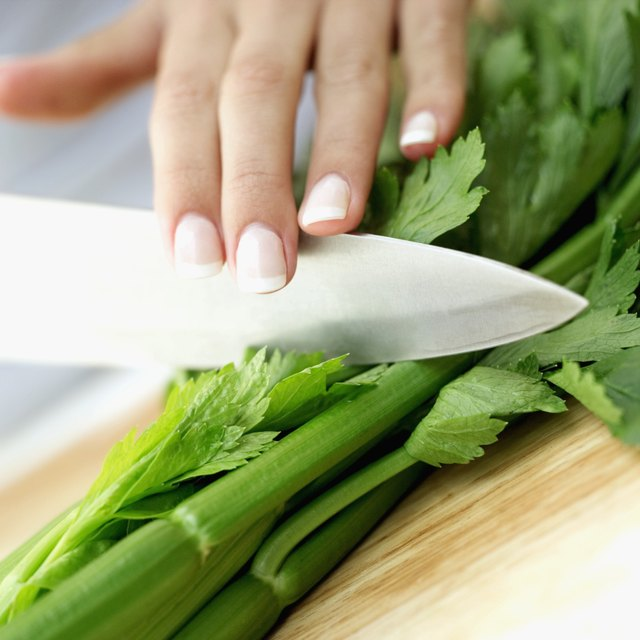 close-up of a woman's hand chopping celery