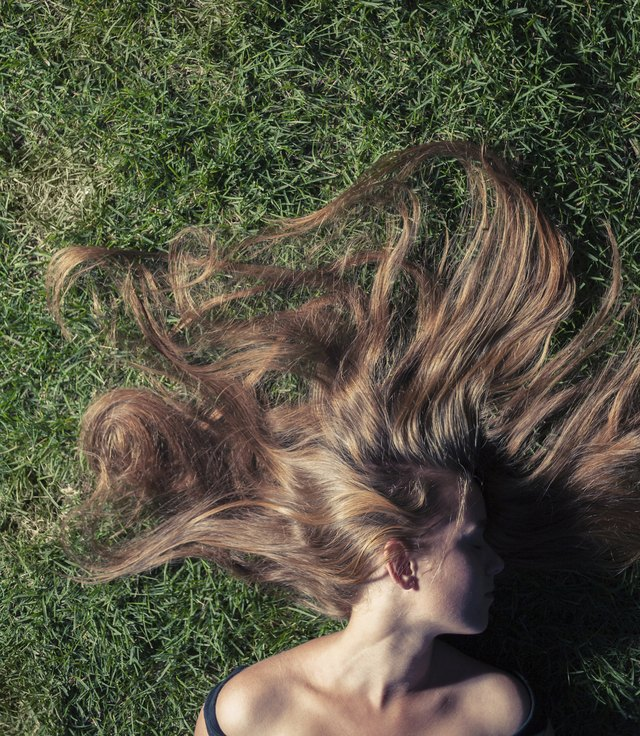 beautiful young girl is lying on green grass