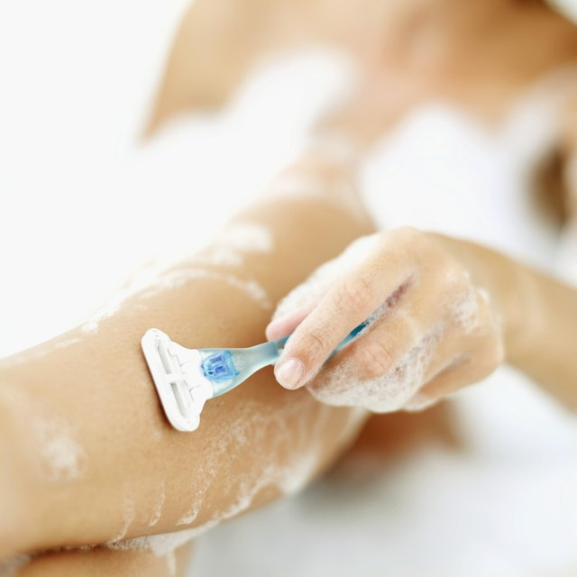 Close-up of a woman's hand shaving her leg in a bubble bath