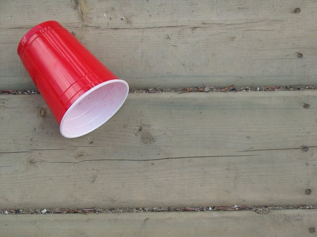 Red Plastic Cup on Wooden Deck Background