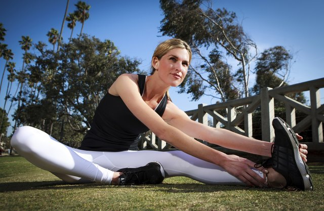 Young blonde woman stretching & exercising in park