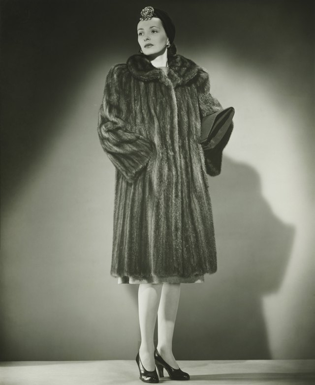 Elegant woman in fur coat posing in studio, (B&W), portrait