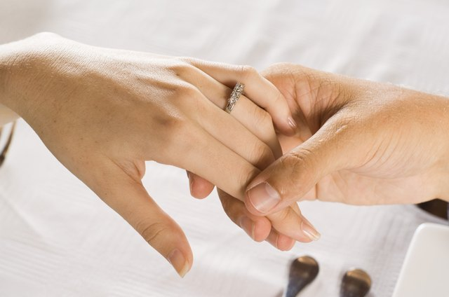 Couple holding hands with engagement ring