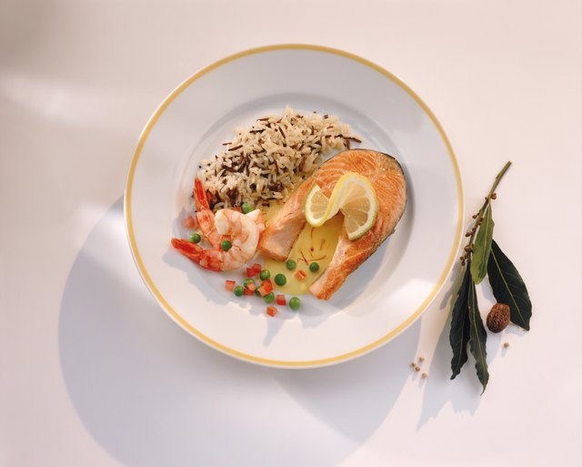 Salmon Cutlet, prawn, wild rice and lemon slice on plate, close-up