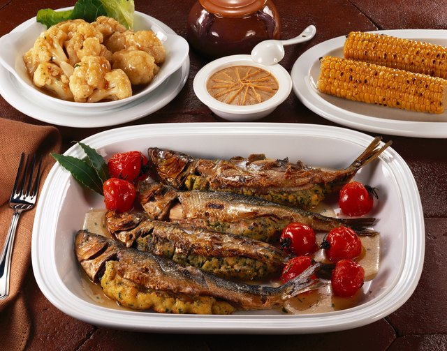 high angle view of stuffed fish served on a platter with side dishes and corn on the cob