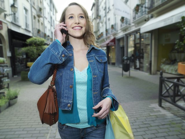 Young woman walking in street using mobile phone, smiling