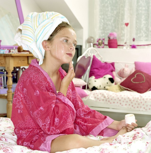 Girl (9-11) with hair in towel sitting on bed applying moisturiser