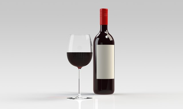 Bottle of red wine with full glass isolated