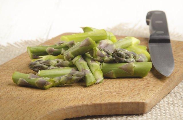 cut €‹green asparagus on a wooden board