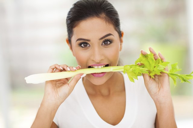 young woman eating a stick of celery