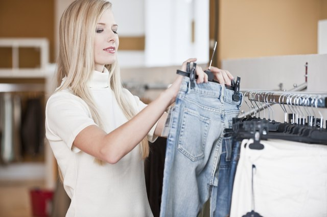 Young woman looking at jeans in a clothes shop