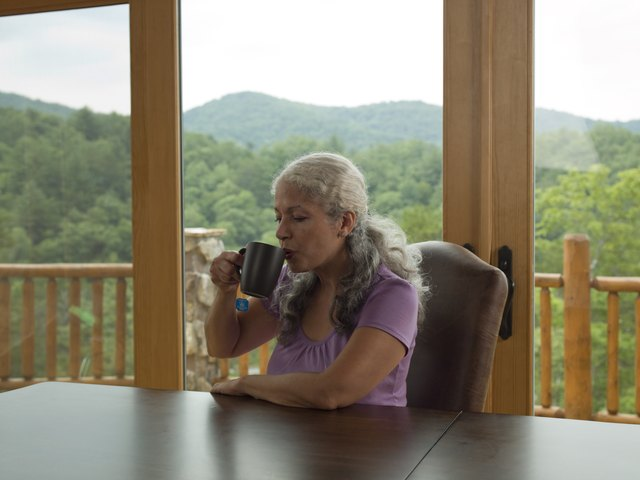 Mature woman sitting at table by window, drinking from mug