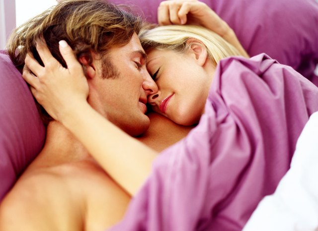 view of a young couple in bed holding each other