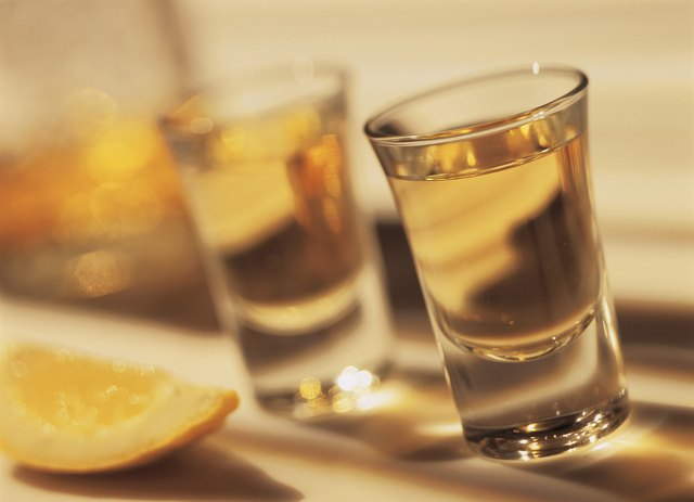close-up of a shot of tequila with a lemon wedge