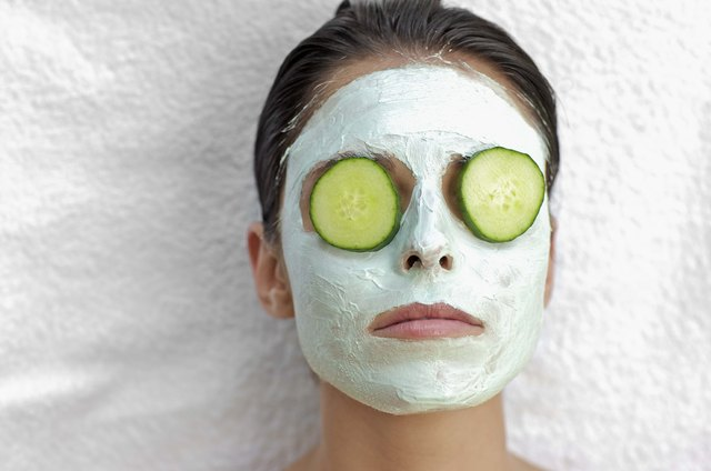 Woman with facial mask and cucumbers over eyes