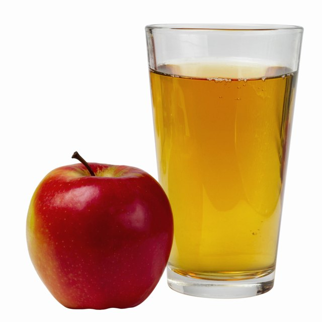 Close up view of an apple and a glass of apple juice