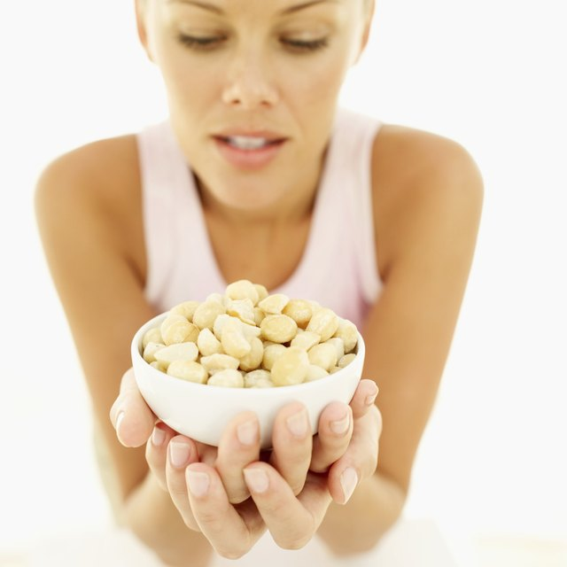 woman holding a bowl of macadamia nuts