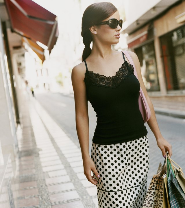 Cool Looking Woman Wearing Sunglasses and a Polka Dot Skirt Carrying Shopping Bags