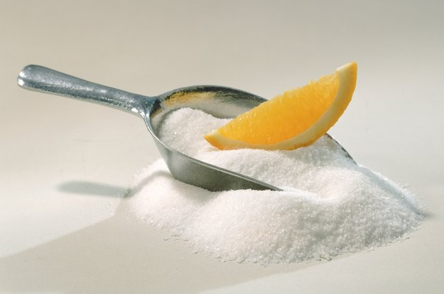 Measuring spoon with sugar and lemon wedge, close-up