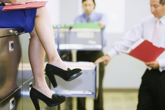Businesswoman on top of a filing cabinet