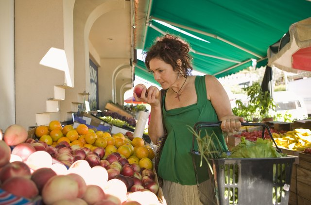 Woman smelling produce at outdoor market