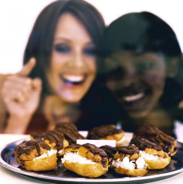 Close-up of two young women looking at a tray of chocolate eclairs