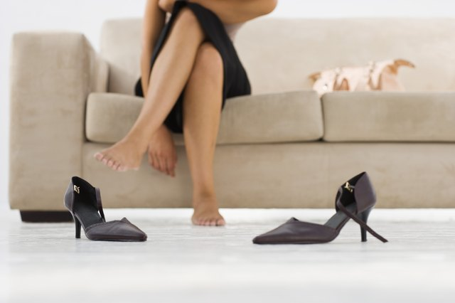High heel shoes and barefoot woman sitting on couch