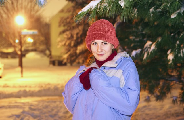 Portrait of young woman wearing blue parka and standing outdoors in winter