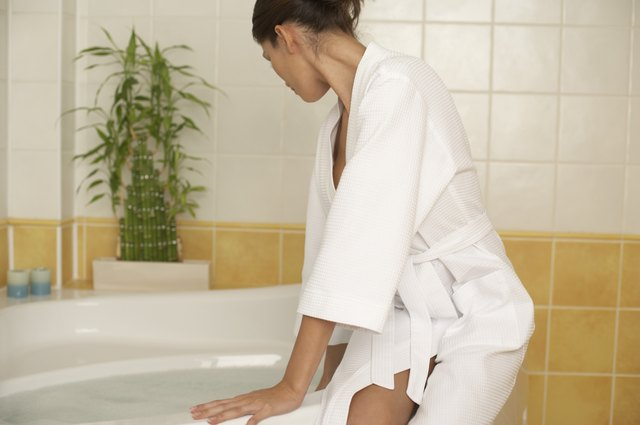 Woman sitting on side of bathtub