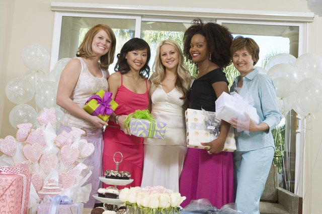 Bride and Friends standing Together holding gifts at Bridal Shower