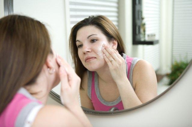 Woman washing face in bathroom mirror