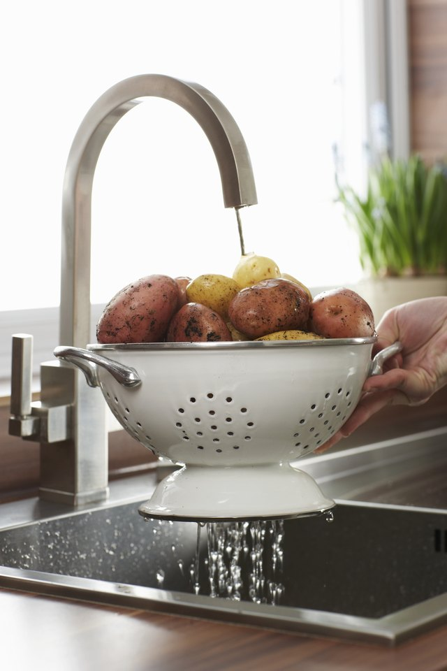 Woman washing raw potatoes at kitchen sink, close-up of hand