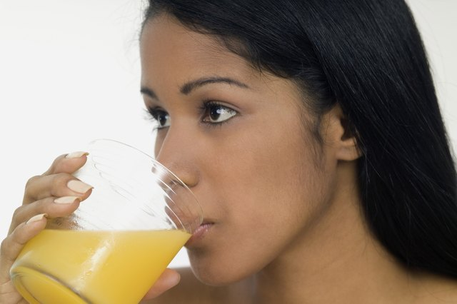 Young woman drinking orange juice, close-up