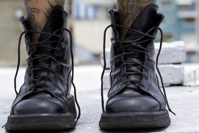 A person with tattooed legs wearing black boots