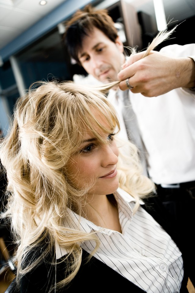 Woman getting hair styled in beauty salon