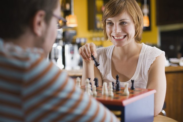 Laughing couple playing chess