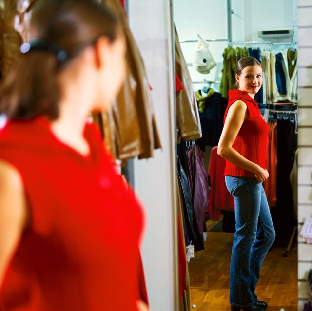 portrait of a young woman trying on a t-shirt