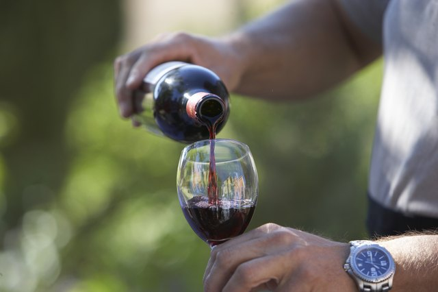 Man pouring wine, close-up of glass